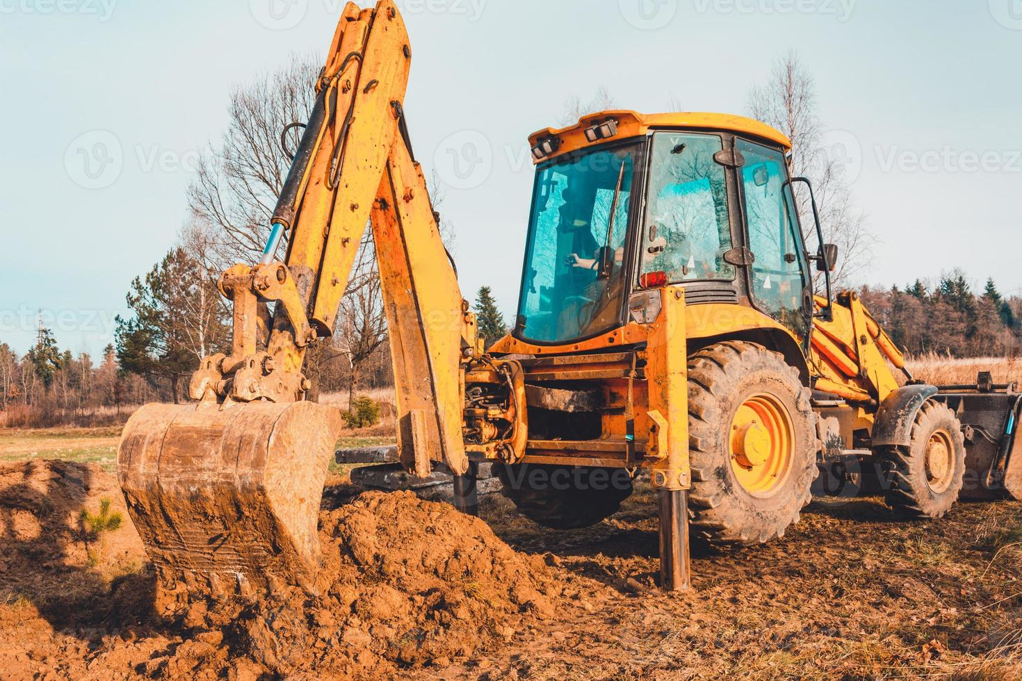 The excavator clears the ground to pave the road in private territory. photo