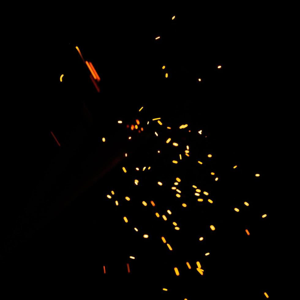 Particles of burning embers fly and glow isolated in the night sky. Blurred bright sparks on black background, yellow hot blurred lights on dark background. photo