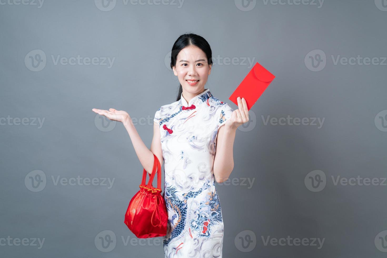Mujer asiática vistiendo traje tradicional chino con sobre rojo o paquete rojo foto