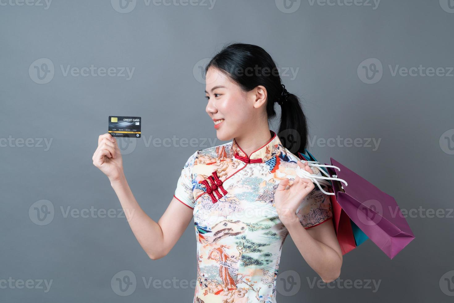 Asian woman wear Chinese traditional dress with shopping bag and credit card photo