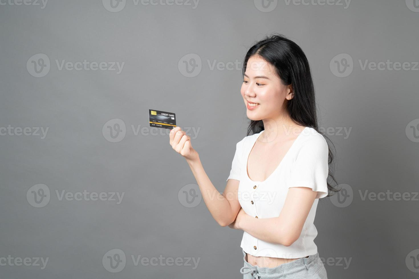 Asian woman with happy face and presenting credit card in hand showing trust and confidence for making payment photo