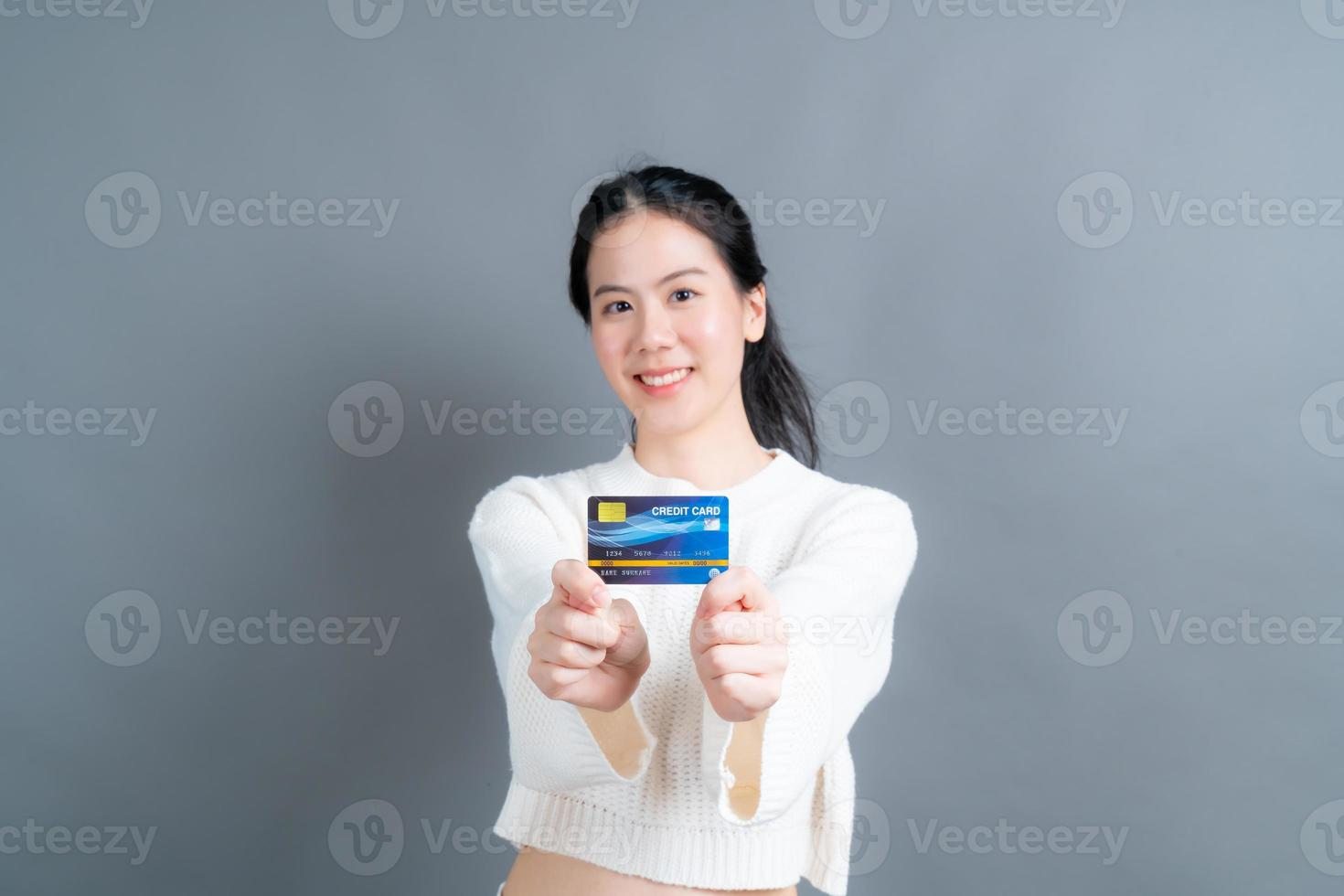 Portrait of a lovely young Asian woman in sweater showing credit card with copy space photo