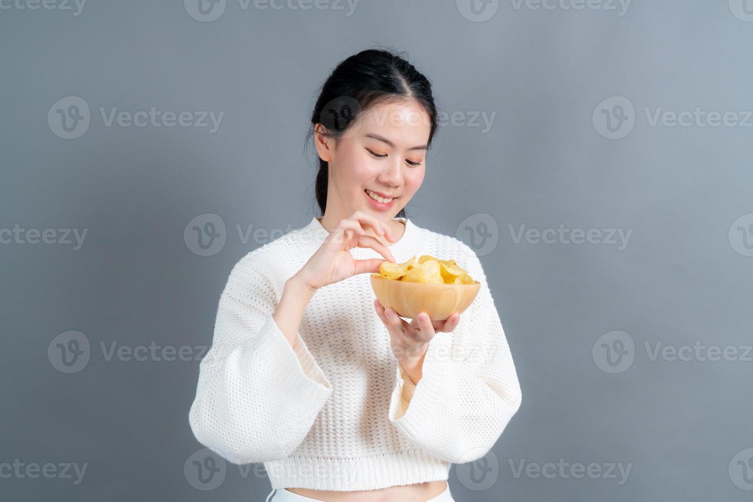 Young Asian woman eat potato chips photo