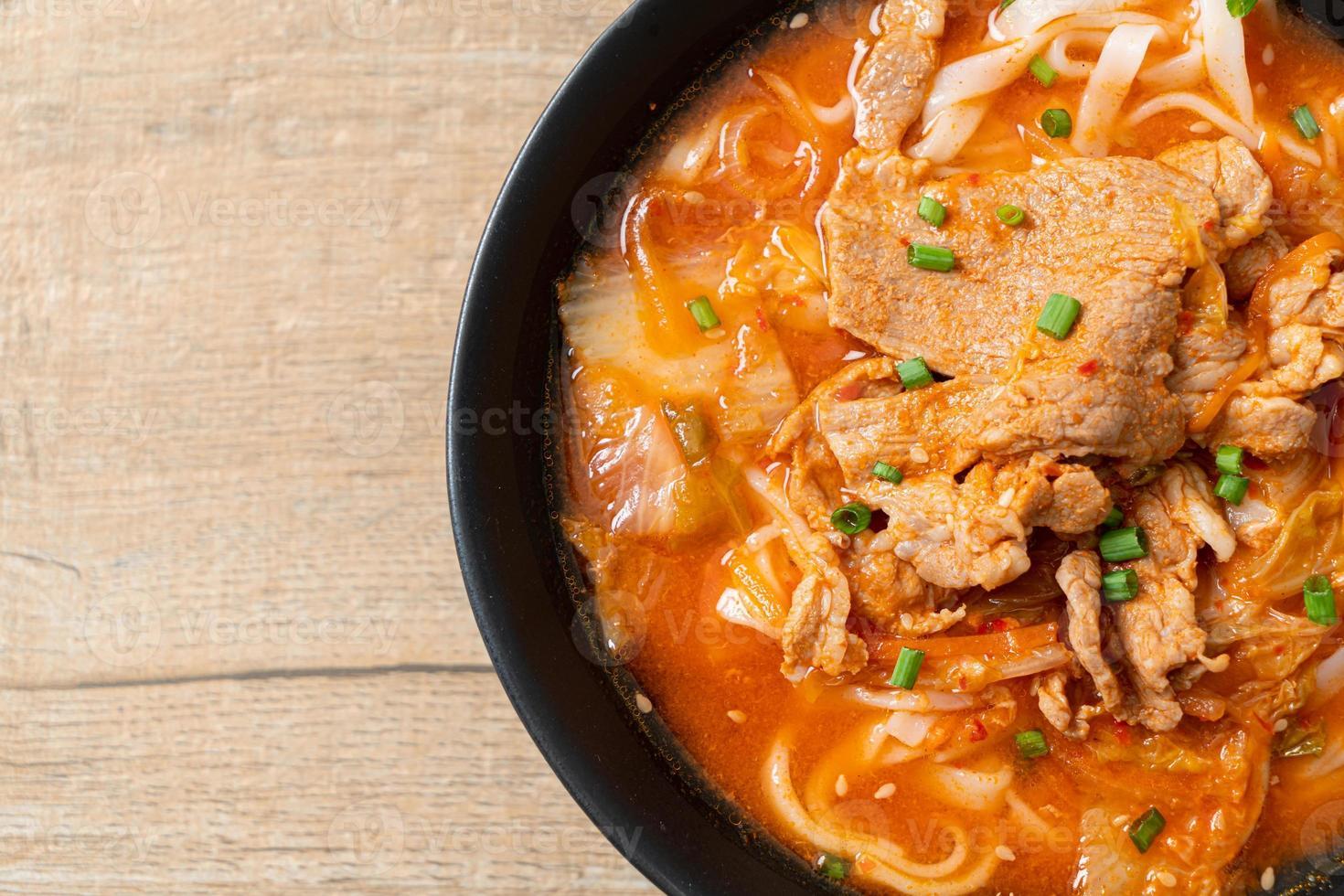 Korean udon ramen noodles with pork in kimchi soup photo