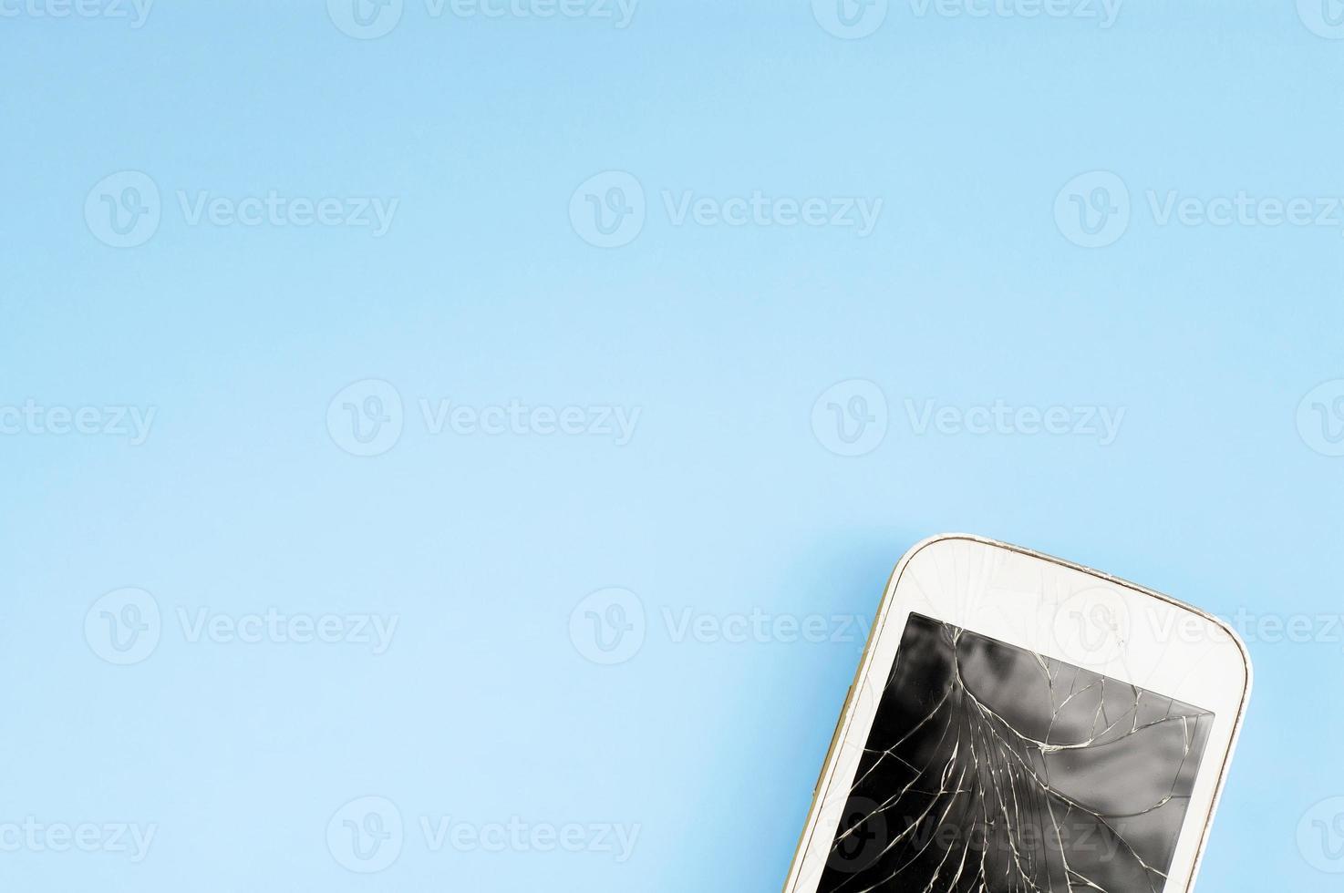 un teléfono celular con pantalla táctil roto sobre fondo azul con espacio libre de copiar y pegar para texto foto