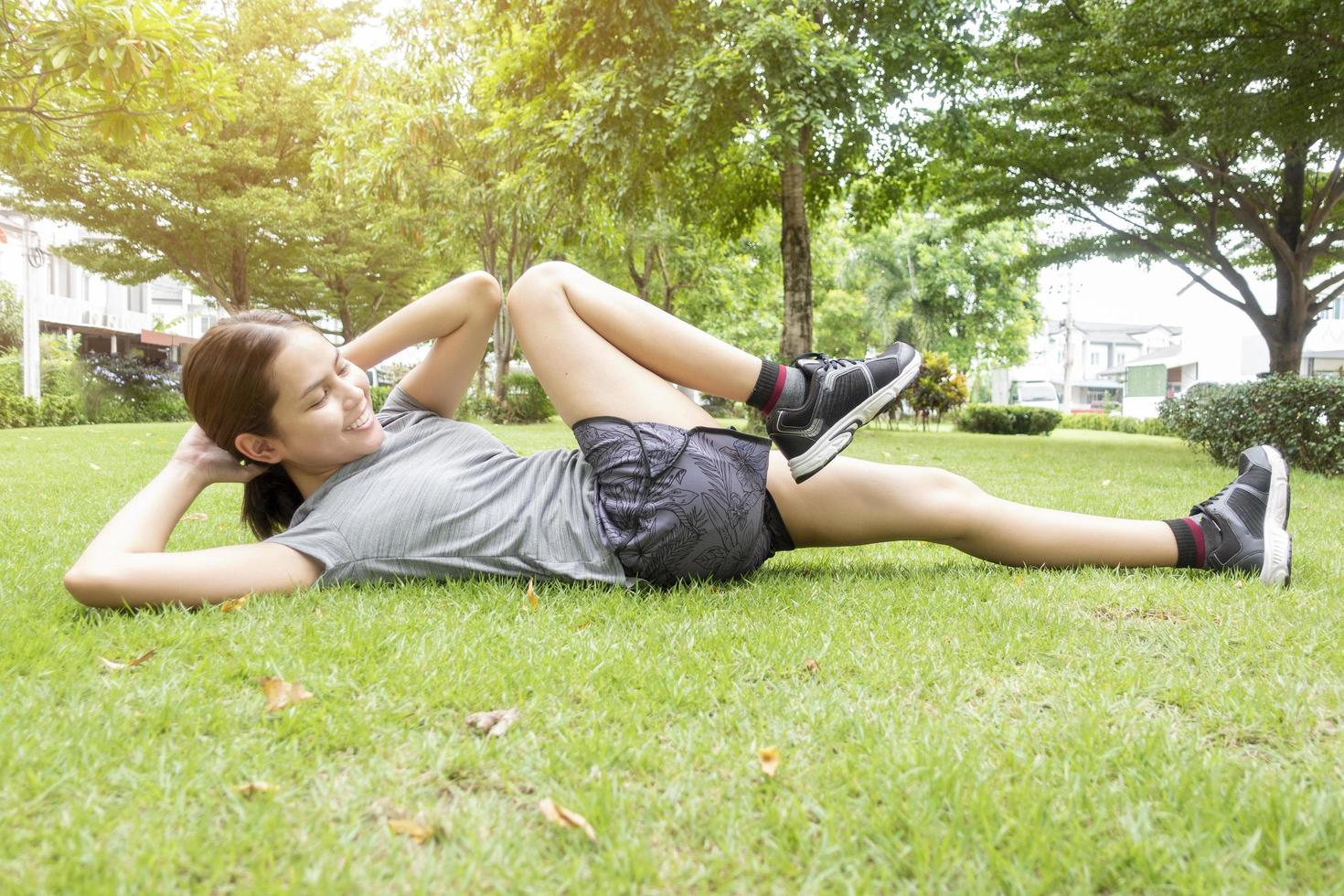 Beautiful sporty woman is doing exercises in green park photo