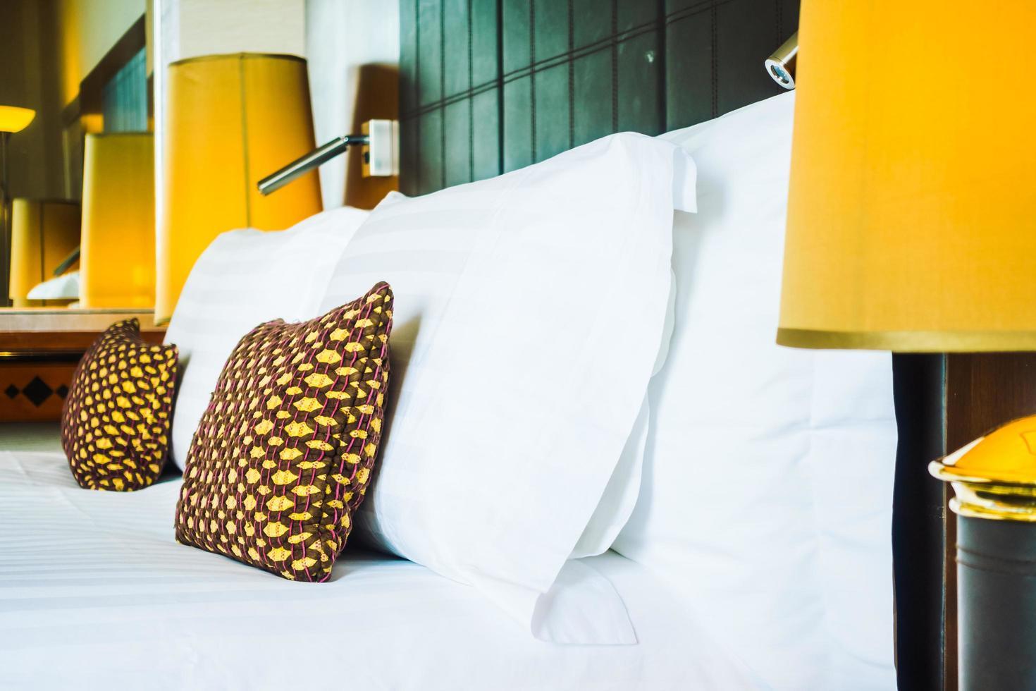 almohada en la cama con lámpara de luz foto