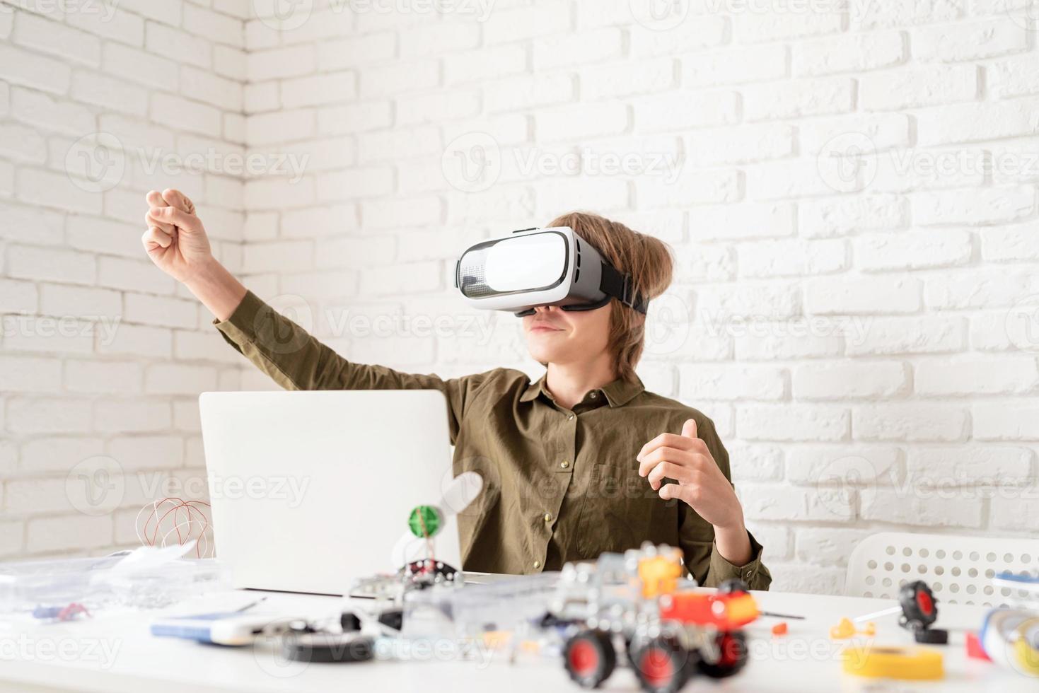 Sonriente jovencito en gafas de realidad virtual jugando el juego foto