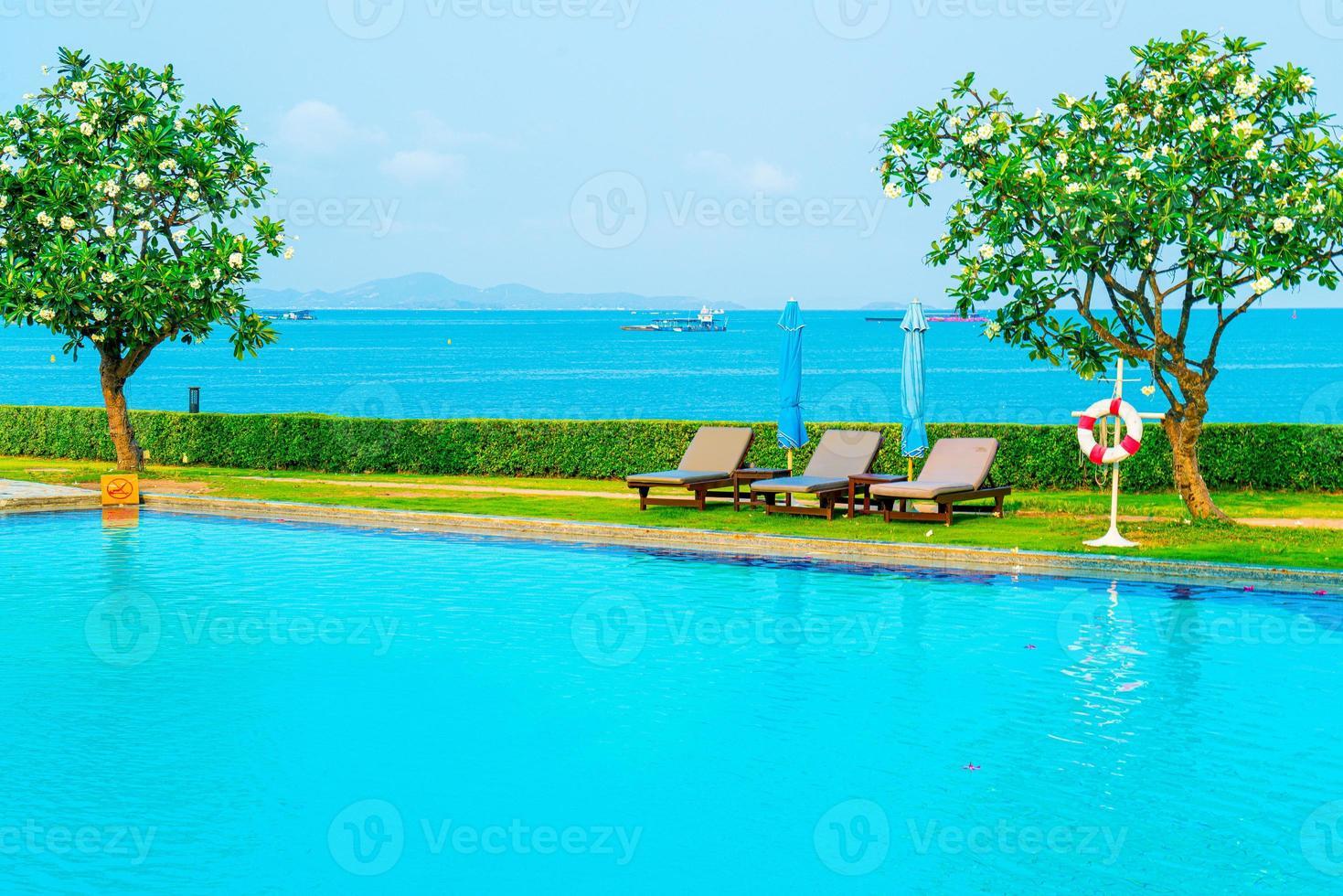 Piscina de sillas alrededor de la piscina con fondo de mar - vacaciones y concepto de vacaciones foto