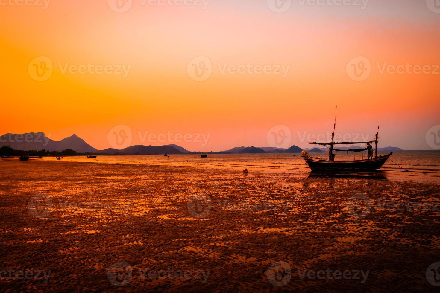 Tropical beach at sunset silhouette background orange sky in Thailand photo