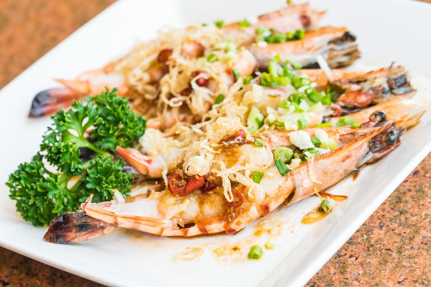 Filete de camarones y langostinos a la plancha en plato blanco foto