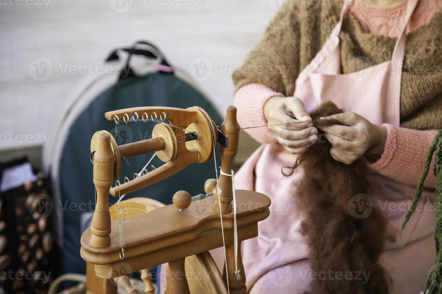 Spinning with a wooden spinning wheel photo