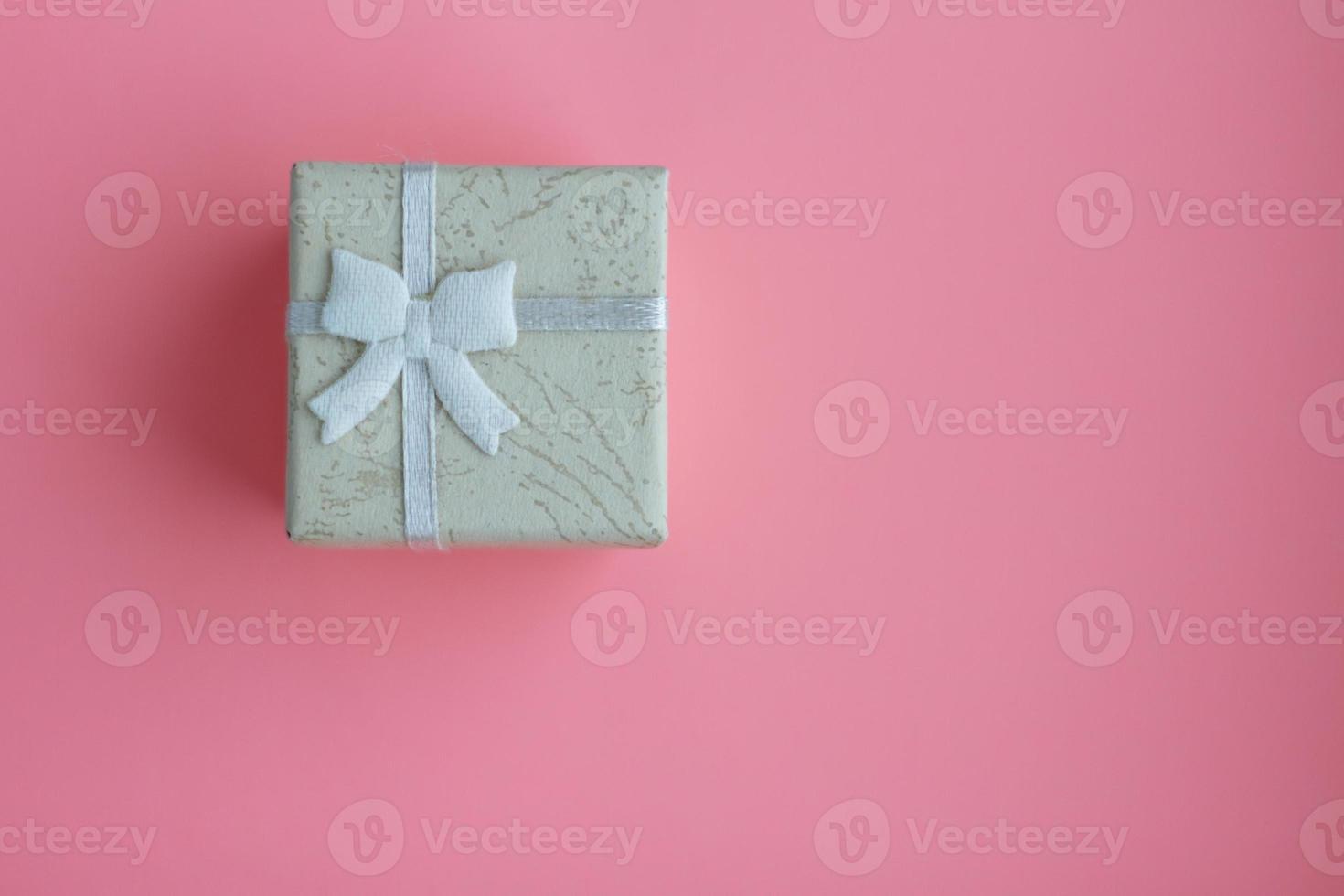 pequeña caja de regalo con cinta sobre fondo rosa foto
