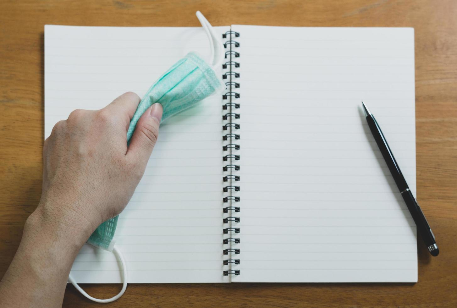 Hand using pen writing phase on the diary book with surgical face mask on top on the sooden table. covid-19, coronavirus and new normal lifestyle concept photo
