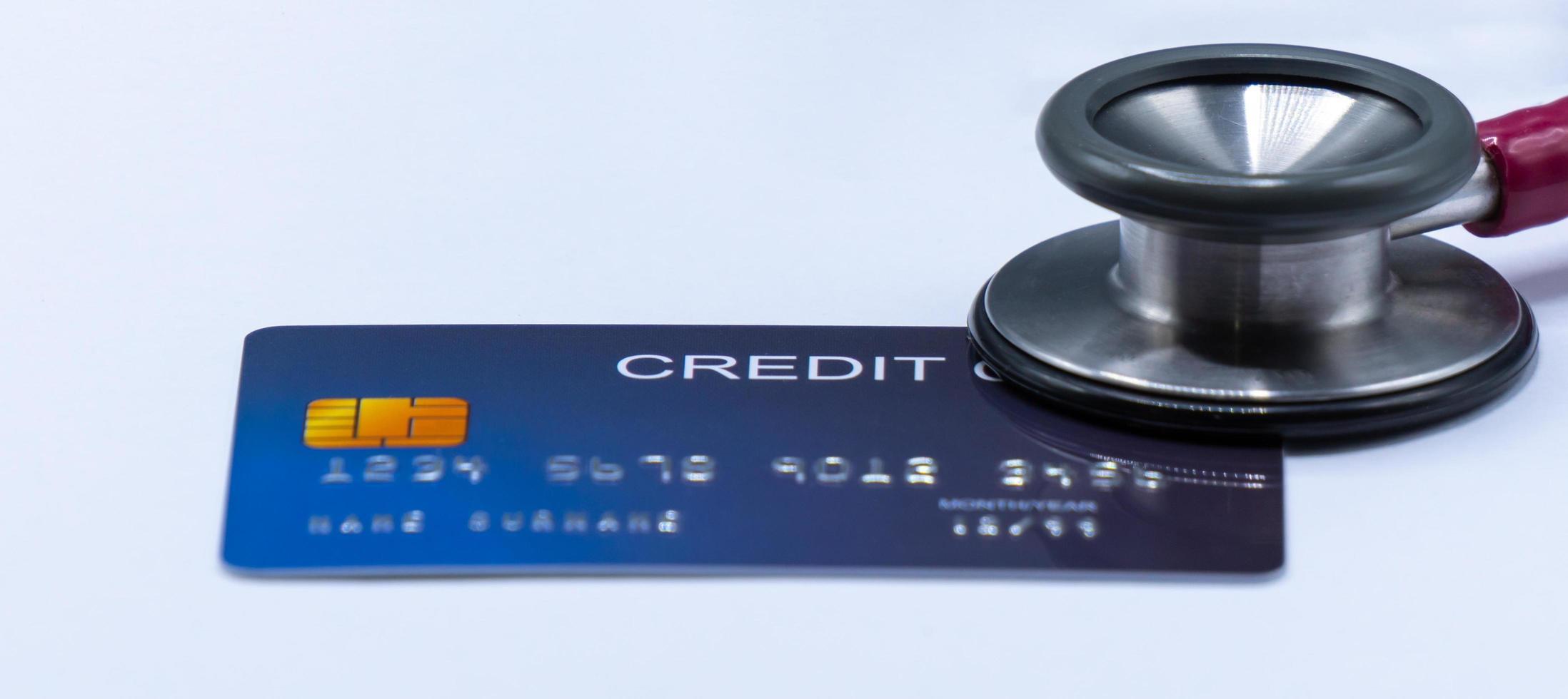 Estetoscopio en la tarjeta de crédito sobre el fondo blanco. foto