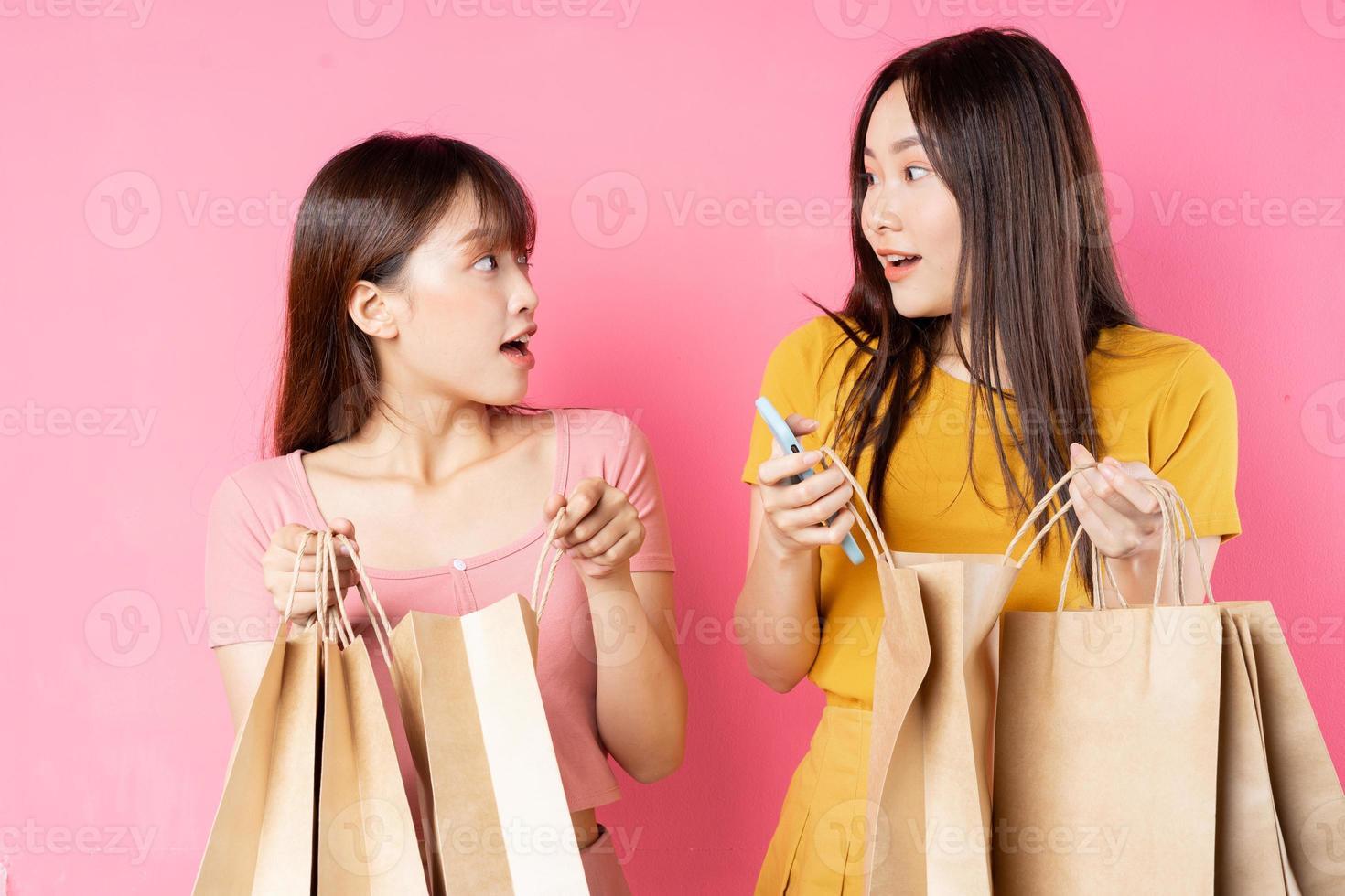 retrato, de, dos, hermoso, joven, niñas asiáticas, tenencia, muchos, bolsas de compras, en, fondo rosa foto