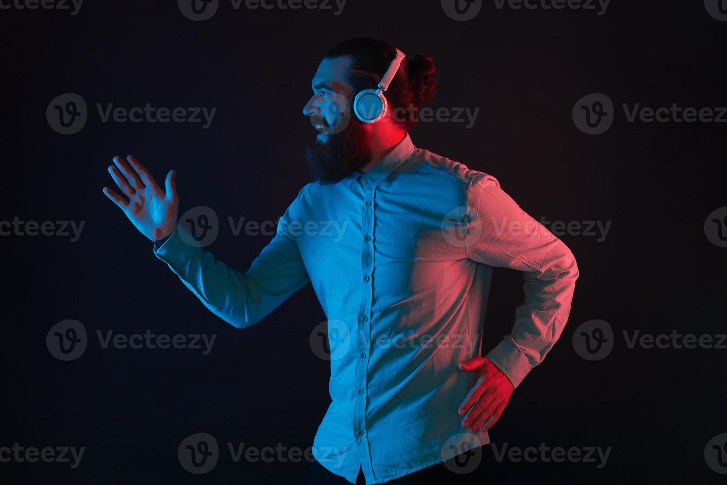 Photo of hipster man with beard wearing wireless headphones and running over dark background with neon light