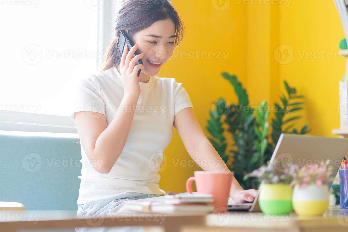 Joven mujer asiática sentada en un sofá trabajando en casa foto