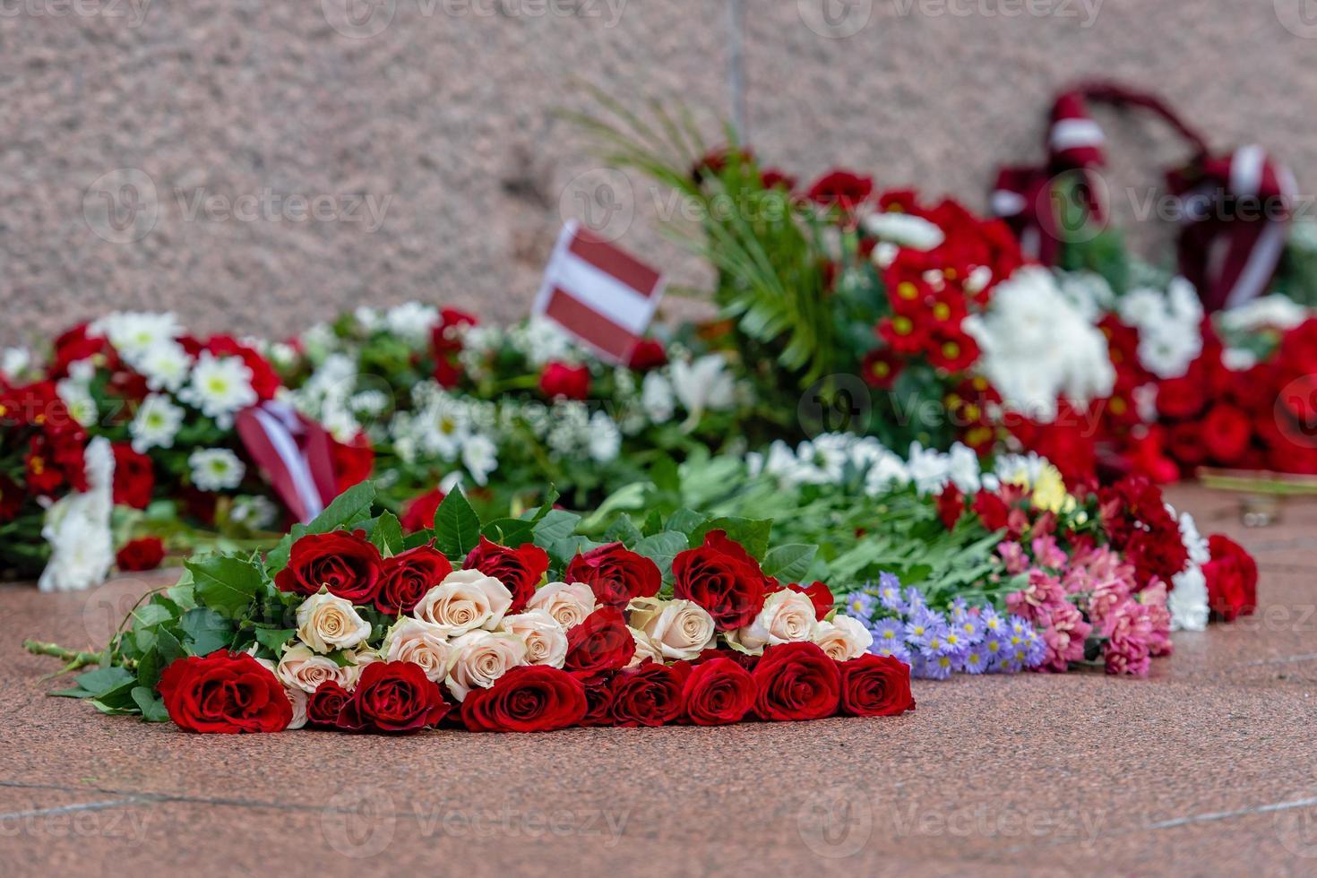 Letonia 100 años. Composiciones de flores rojas y blancas en el monumento a la libertad en la ciudad de Riga, Letonia. foto