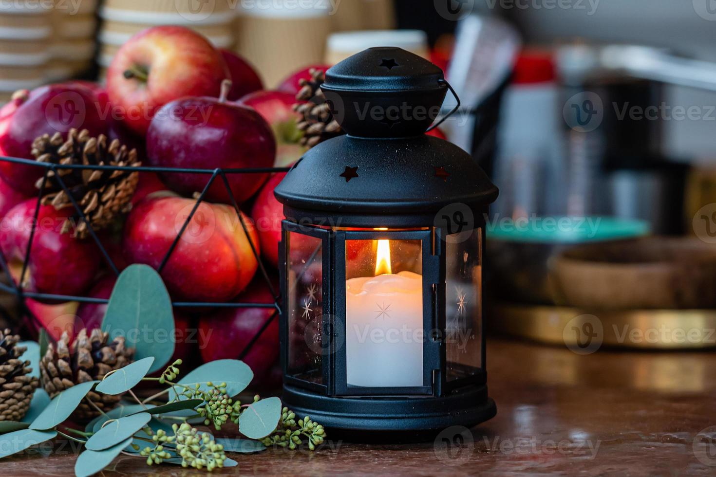 Glowing candle lantern and basket of apples on the table in the Christmas Market in Riga, Latvia photo