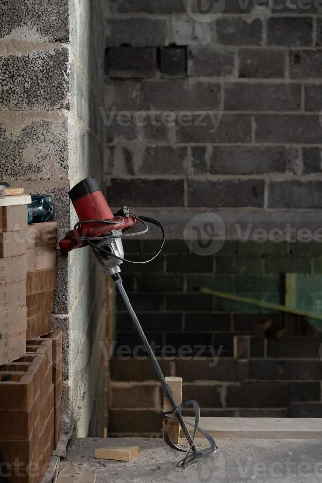 Electric drill with a mixer in a newly constructed building. photo