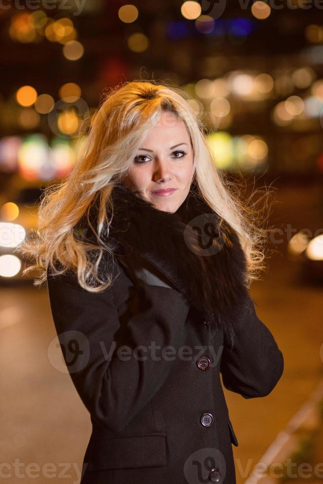Beautiful, blonde woman in car lights in the night city. photo