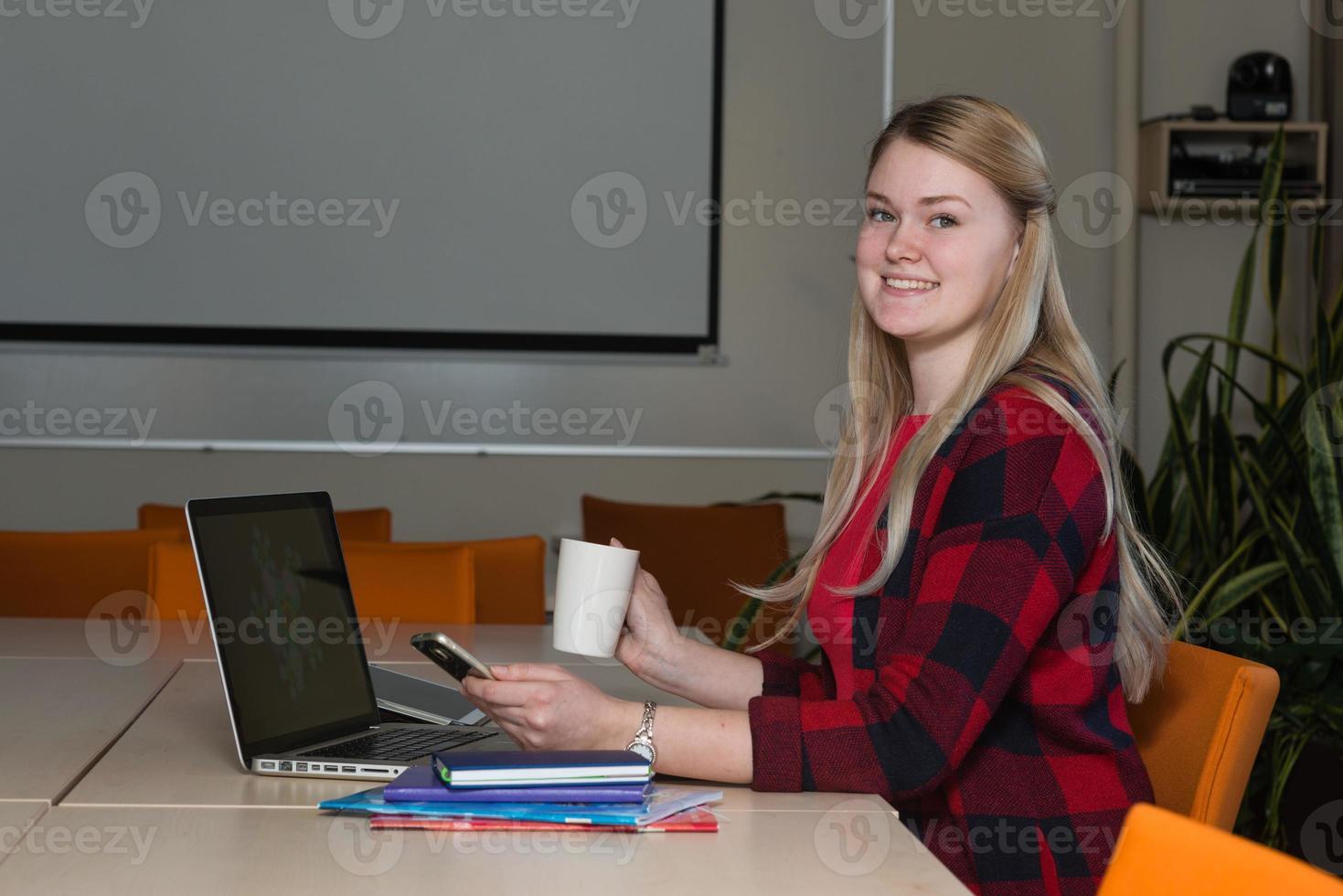 sonriente mujer rubia sentada en una computadora portátil bebiendo té y trabajando. foto