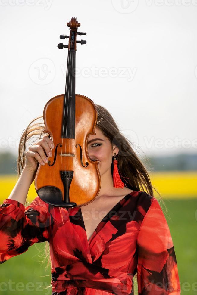 retrato de una mujer joven positiva. parte de la cara está cubierta por el cuello del violín - imagen foto