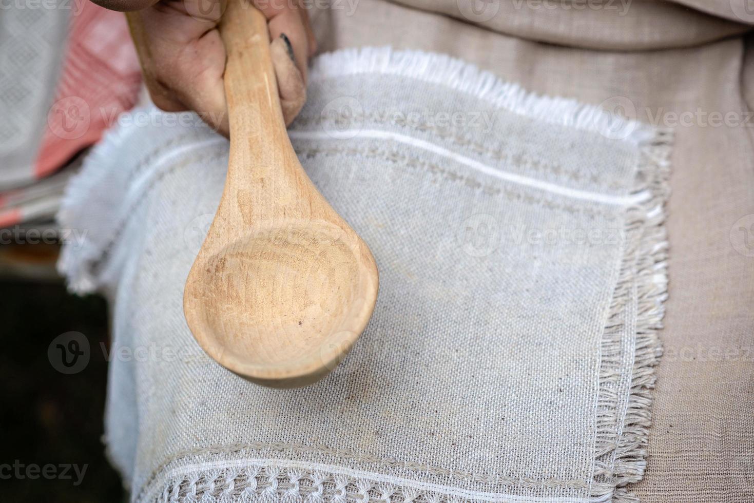 Mujer haciendo cuchara de madera artesanal tradicional foto