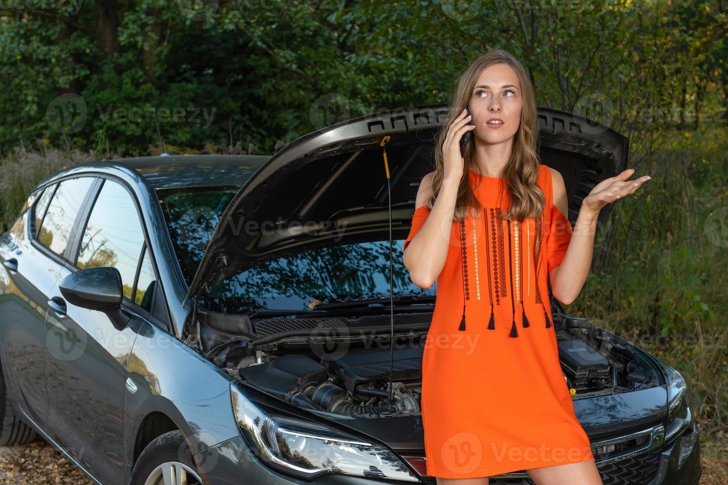 bonita y joven mujer junto a la carretera después de que su coche se averió foto
