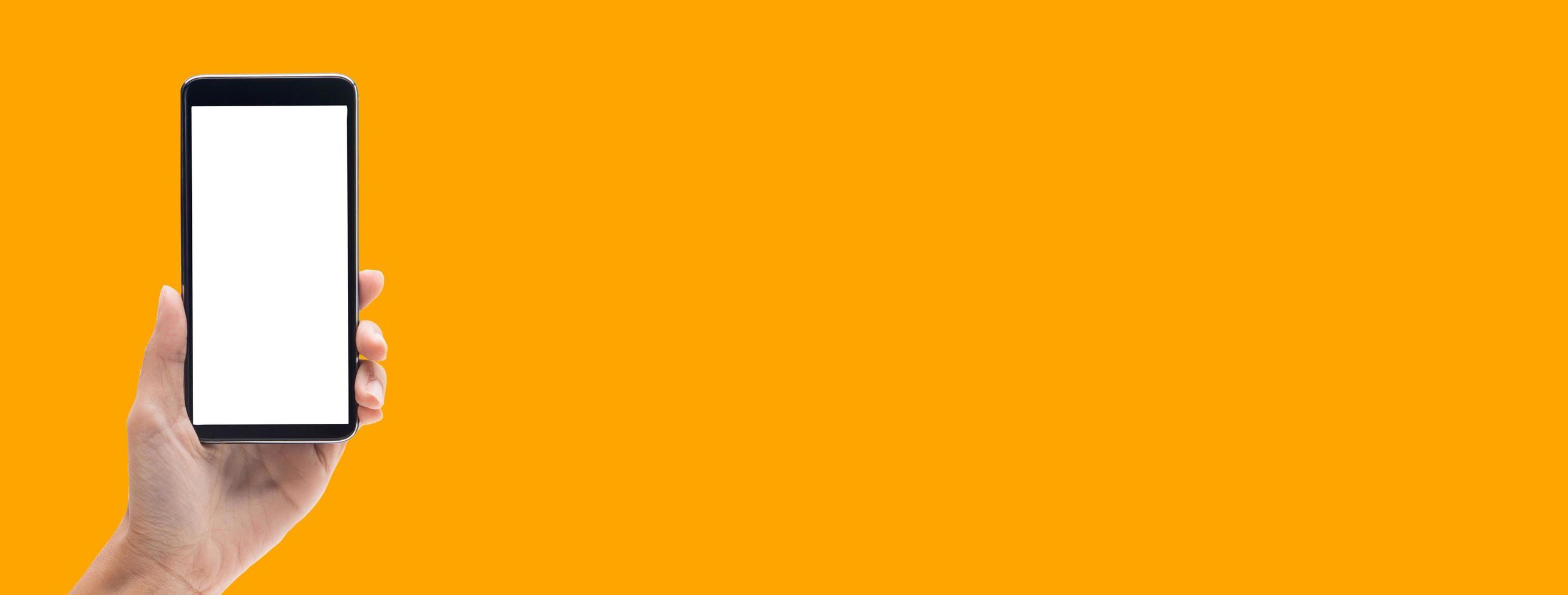 Hand holding smartphone on orange banner background photo