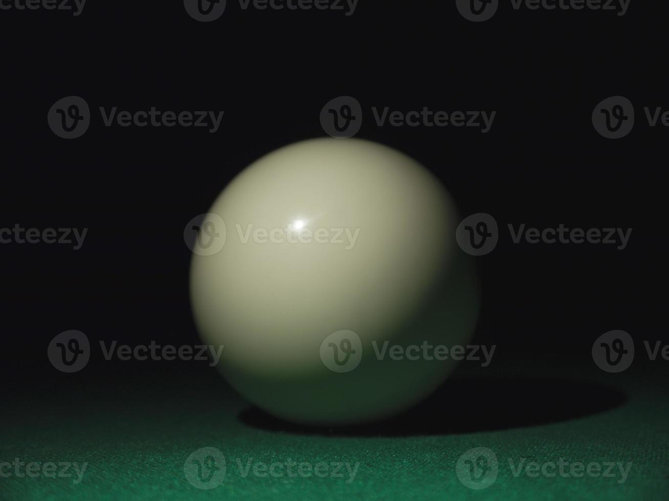 White ball on a billiard table in the dark photo