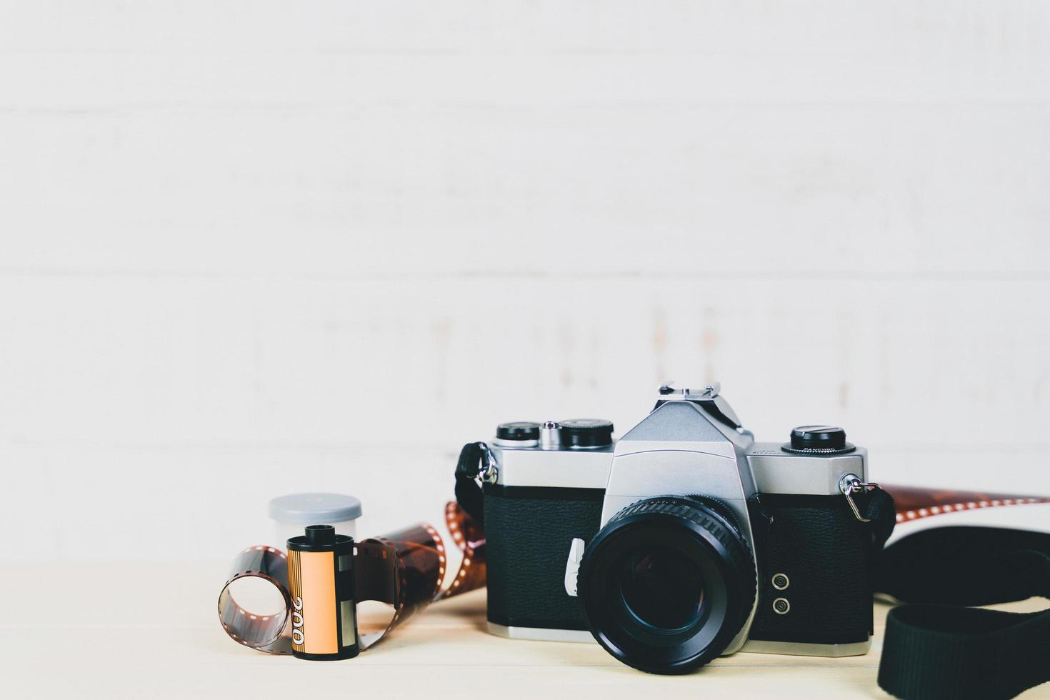 Old 35mm SLR film camera and a roll of film on wooden background. Flim photography concept. photo