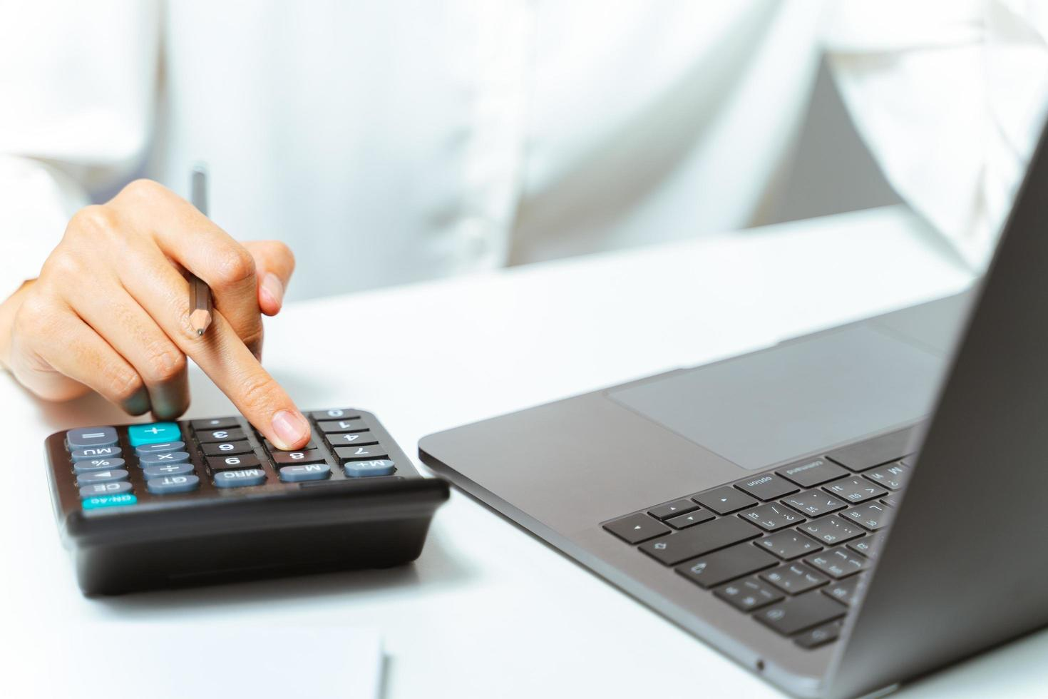 Close up of woman hand using calculator and computer laptop in home or office. photo