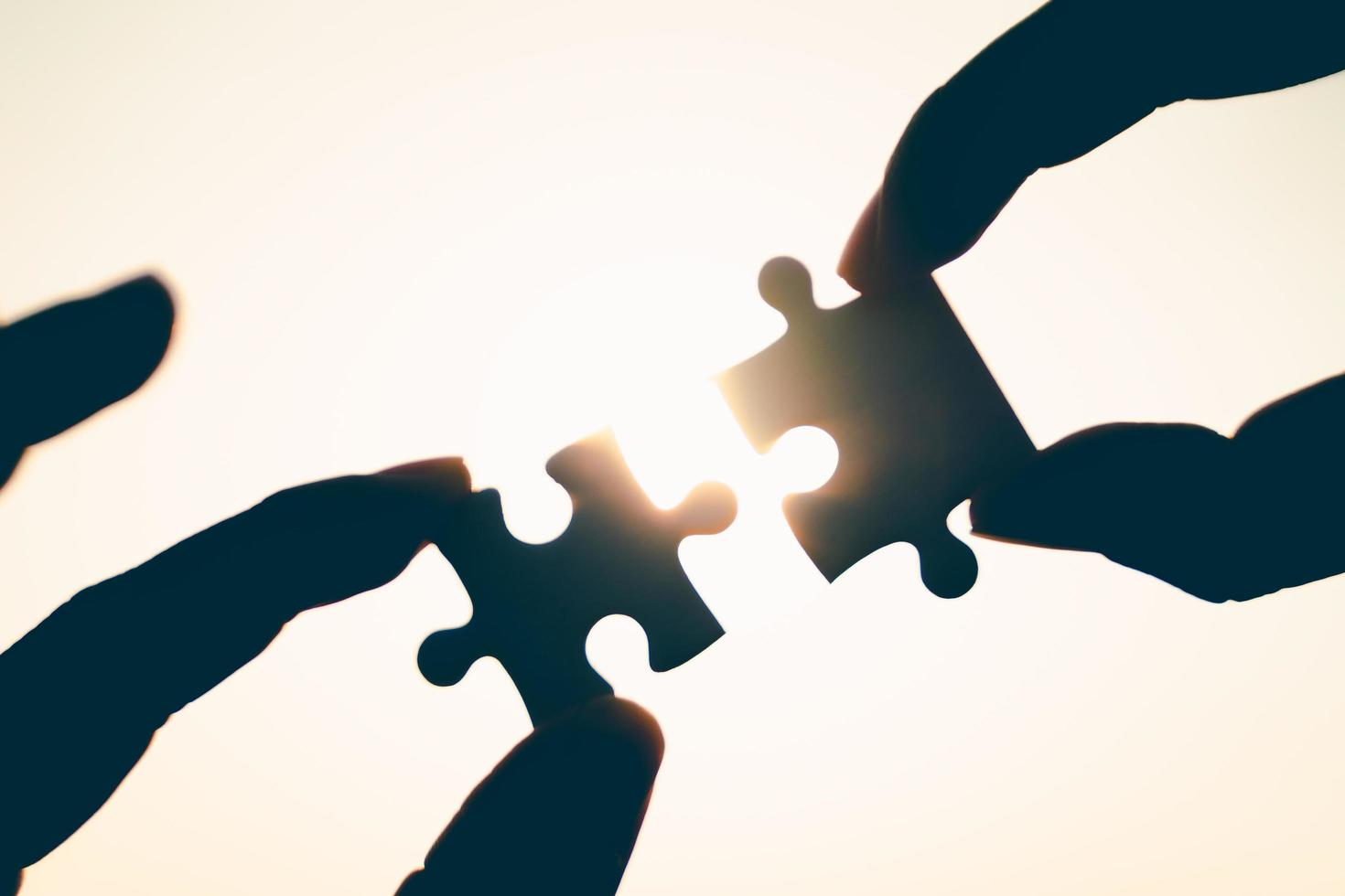 Silhouette of closeup woman and man hand connecting a piece of jigsaw puzzle over sunlight effect. symbol of association and connection concept. business strategy. photo