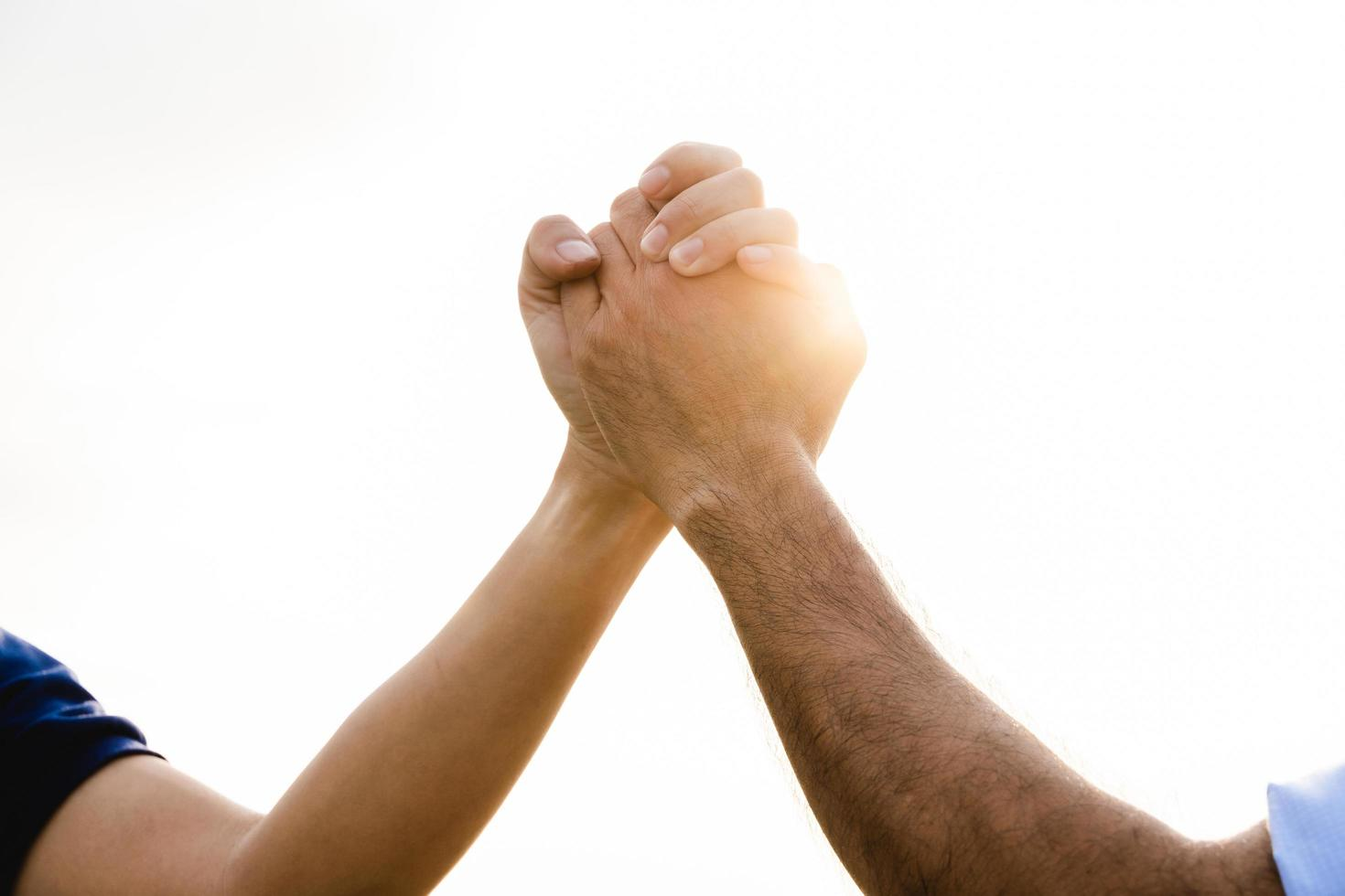 Closeup of two holding Hands on the sky background. Friendship, Helping Concept. Friendship Day. photo