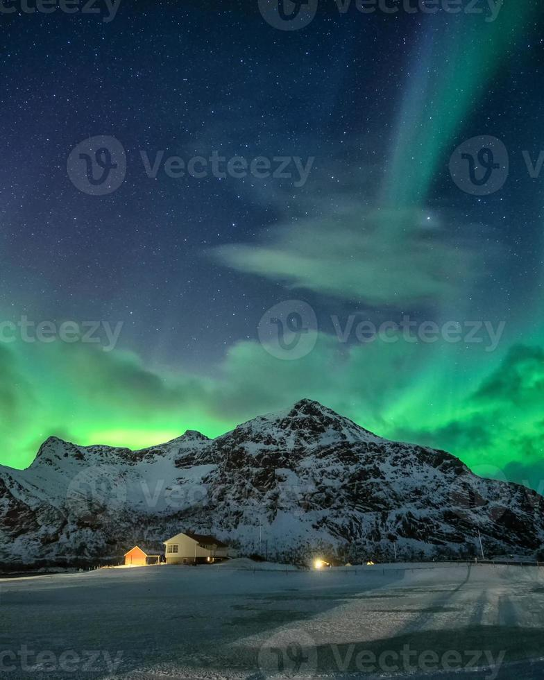 Aurora Borealis with starry over snowy mountain and nordic village at night in Flakstad, Lofoten Islands photo