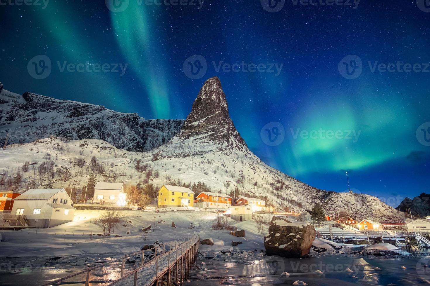 Colorful scandinavian village with northern lights over peak mountain at Lofoten photo