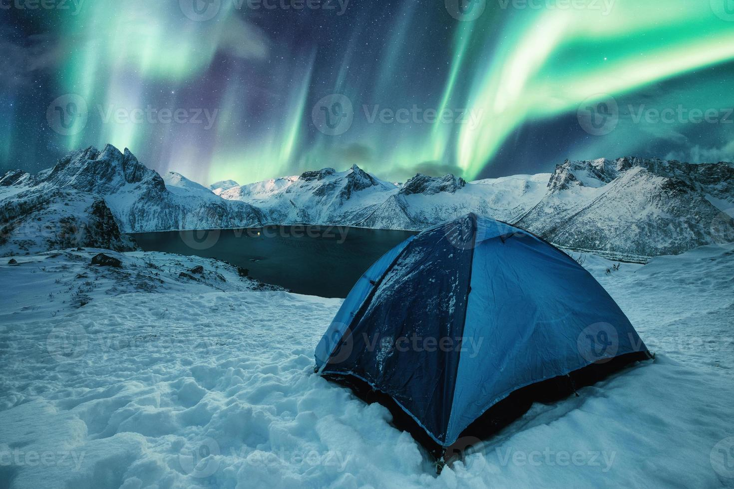 Blue tent camping on snowy hill with Aurora Borealis dancing on mountain range in Senja Island photo