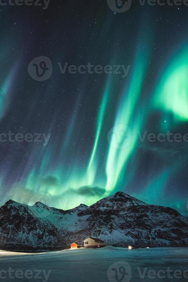 Aurora borealis, Northern lights with stars glowing on snowy mountain in the night sky on winter at Lofoten Islands photo