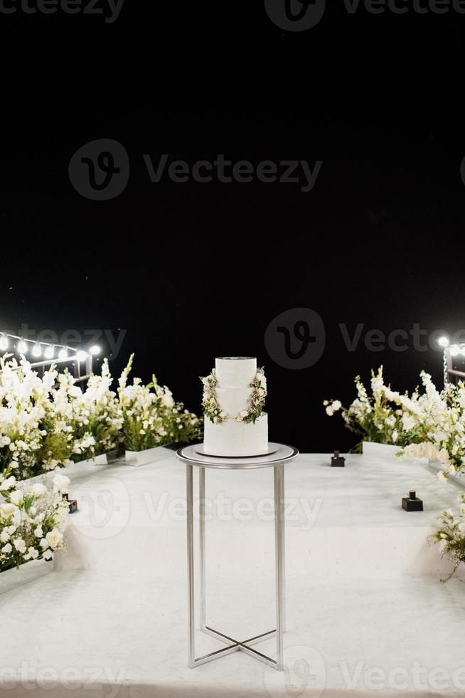 wedding white cake on a high stand near the white podium photo