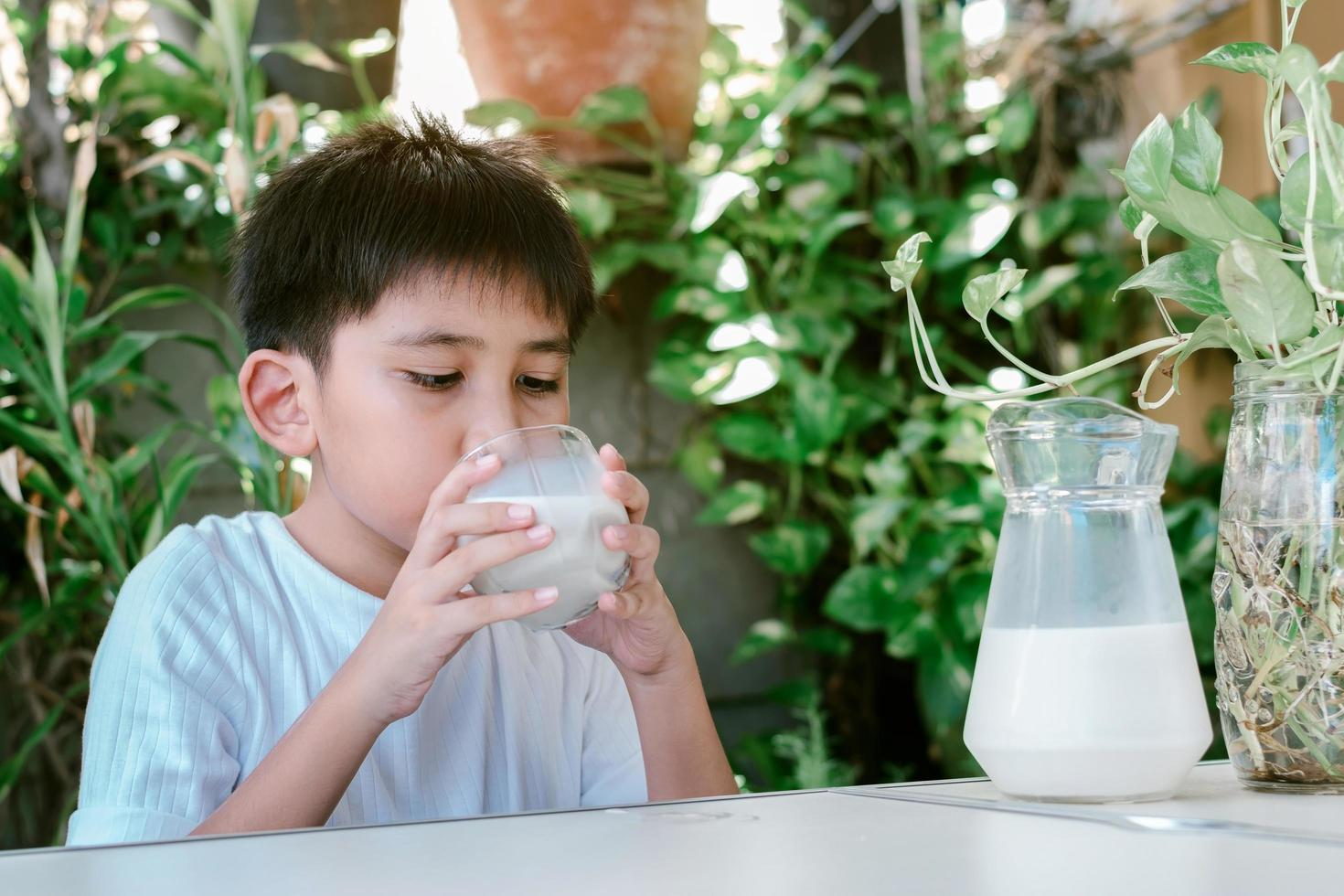Asian boy in a white T-shirt is drinking a glass of milk photo