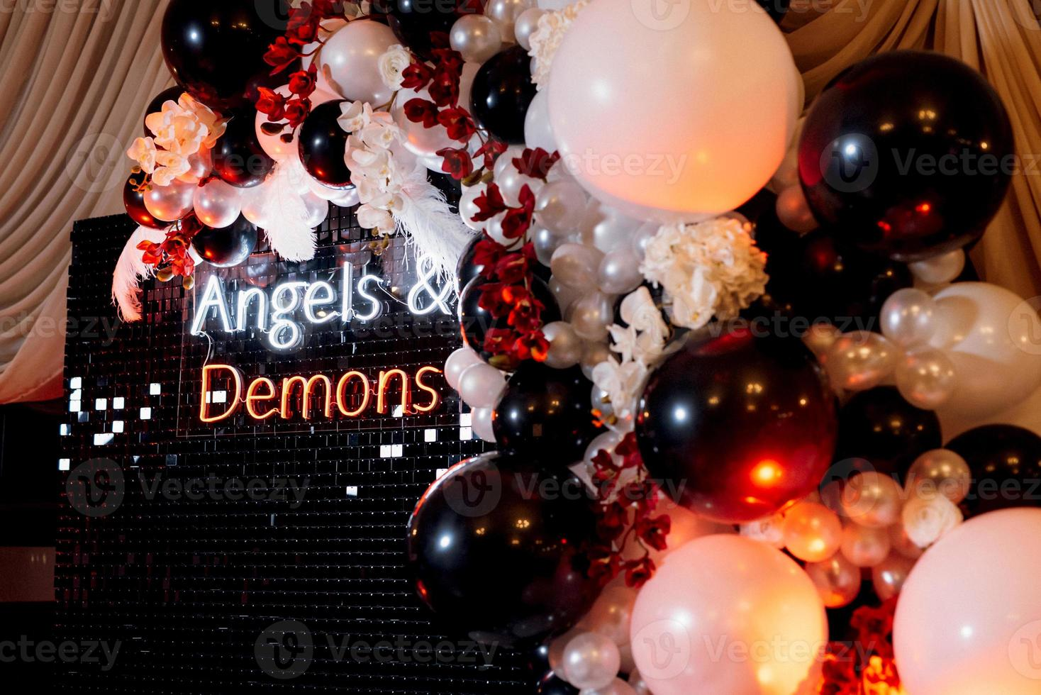 a photo zone themed angels and demons in black with white and black balls