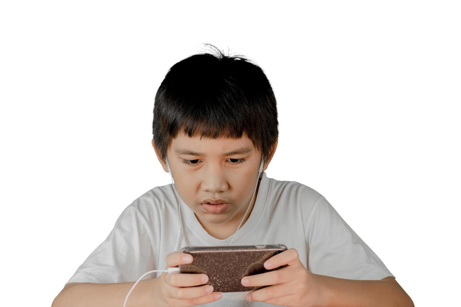 Chico asiático usando audífonos jugando juegos en teléfonos inteligentes. foto