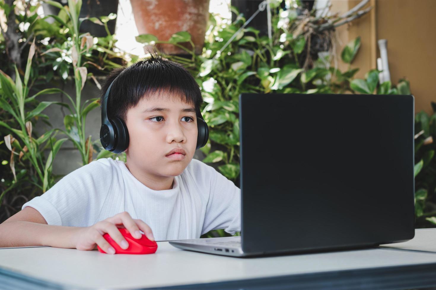 niño asiático usa auriculares inalámbricos y usa una computadora portátil para estudiar en línea foto