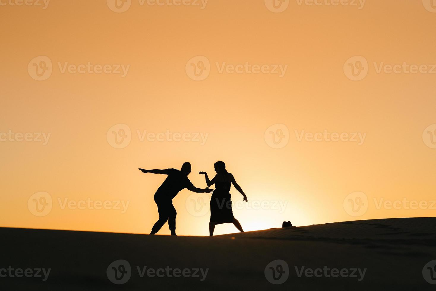 silhouettes of a happy young couple guy and girl on a background of orange sunset in the sand desert photo