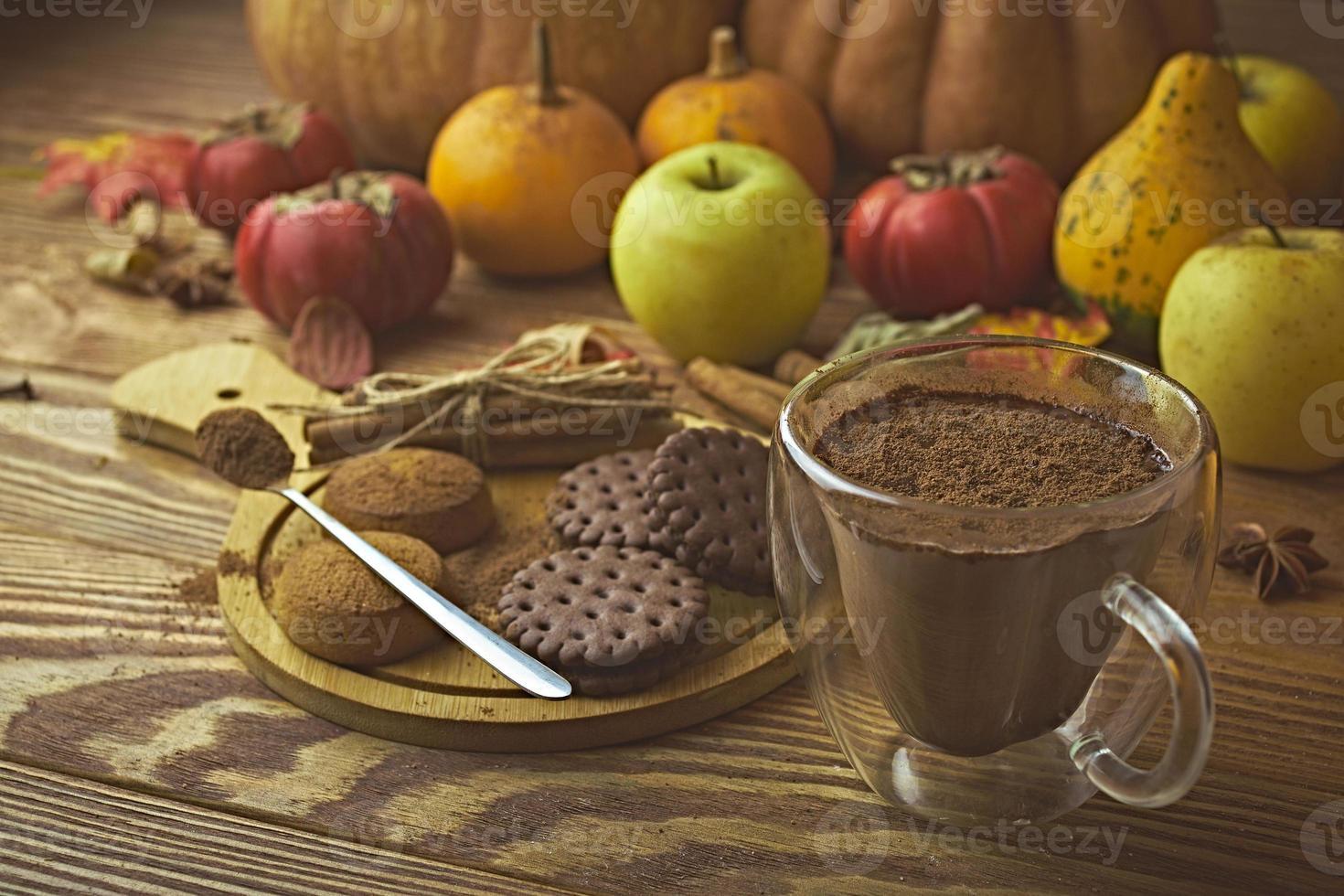 chocolate caliente, galletas y cosecha de otoño en mesa de madera. foto