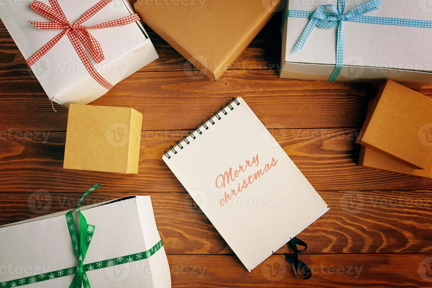 Top view of Merry Christmas notebook and gift boxes on wood table background. photo