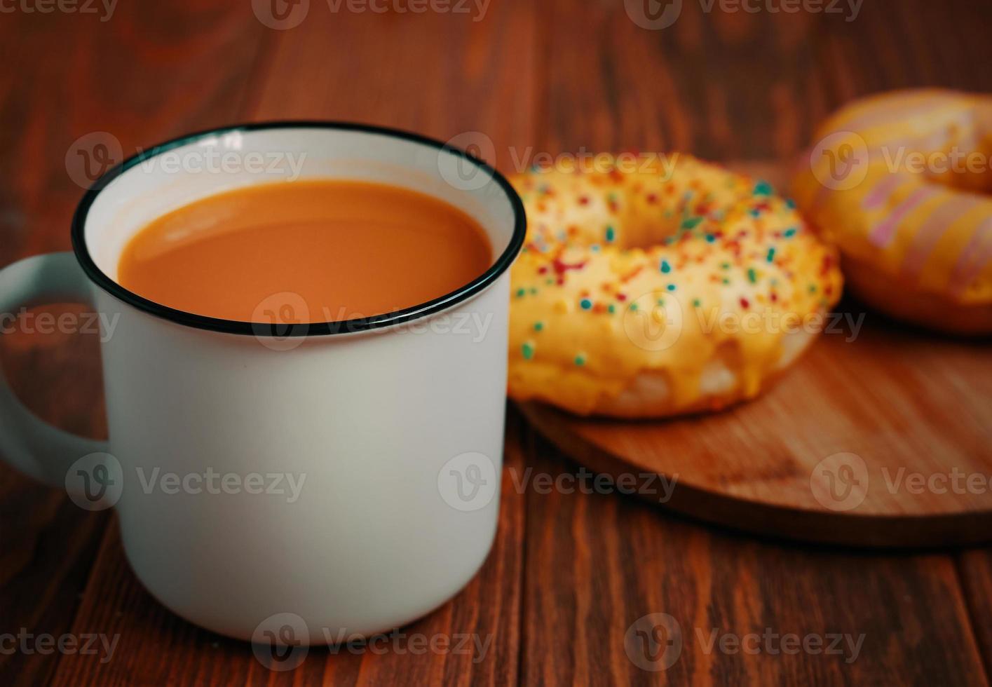 taza de jugo de calabaza y dos rosquillas dulces con glaseado de limón. foto