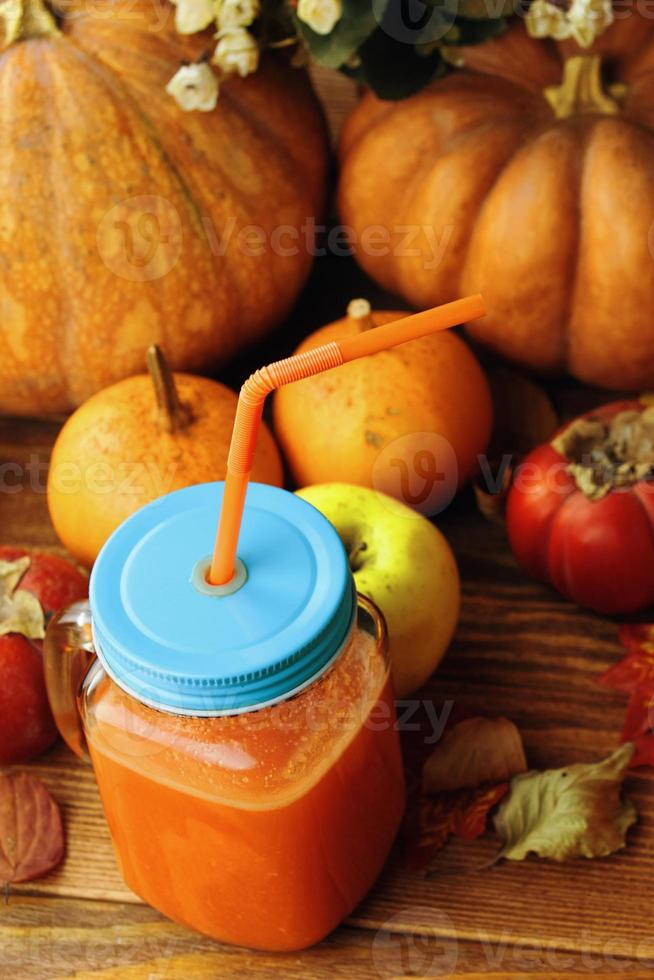 Glass of fresh pumpkin smoothie on a wooden background. photo